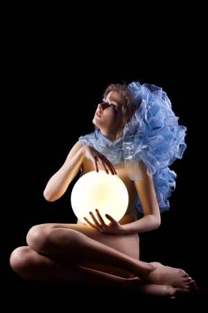 Studio portrait of beautiful young woman holding light lamp photo