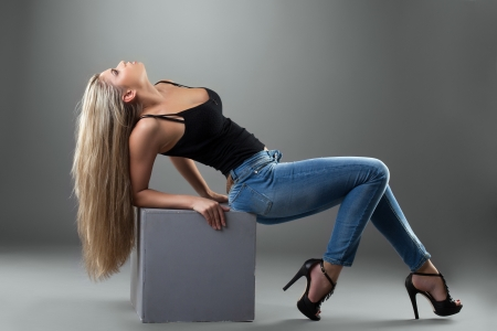 Sexy blonde woman in jeans posing in studio photo