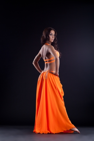 Full length portrait of oriental dancer in orange costume photo