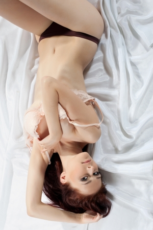 Sexy brunette woman lying on white sheet photo