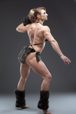 only the biceps: Full length portrait of woman body builder