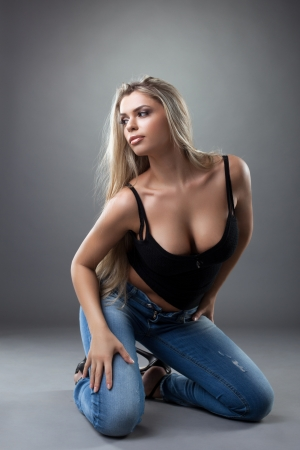 beautiful sexy young woman posing in black top and jeans photo