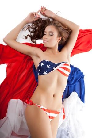 niñas en bikini: joven mujer sexy en bikini bandera de EE.UU. en el tejido aislado en blanco