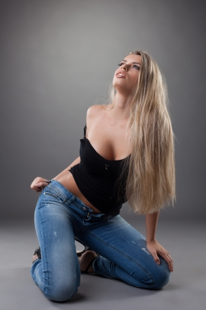 beautiful sexy woman posing in black top and jeans photo