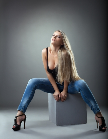 Blonde sexy girl in studio sit on cube photo