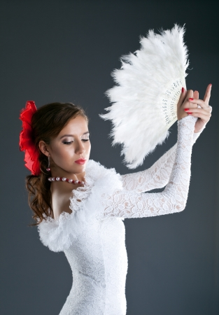 woman posing in flamenco white costume with fantail photo