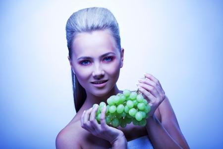 Cold young woman take frozen grapes portrait photo