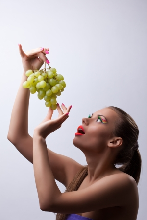 sexy food: Sexy young woman eat green grapes, glow make-up