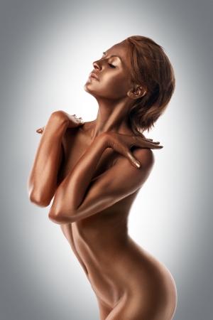 mujeres negras desnudas: Mujer joven desnuda con piel de metal posando como estatua
