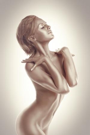 modelo desnuda: La mujer con el cuerpo desnudo perfecto como la estatua de metal de maquillaje
