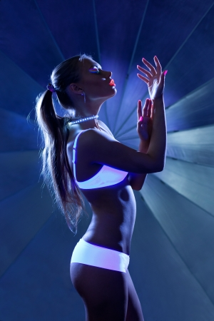 Girl with ultraviolet make-up disco dance in dark photo