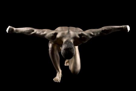 naked man: Hombre fuerte desnudo con la piel de oro constituyen posando en la oscuridad