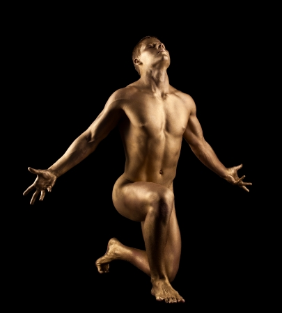 Athletic naked man show perfect body with gold skin