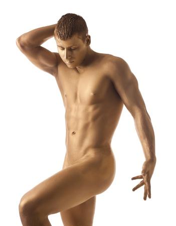 hombre desnudo: Hombre atlético posando desnuda en la oscuridad con la piel de oro aislado Foto de archivo
