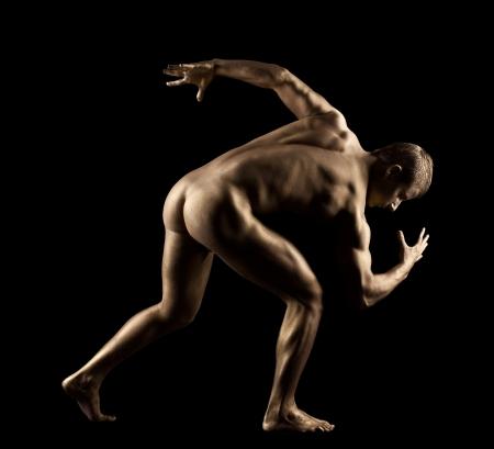 naked statue: Athletic man posing nude in dark with metal skin