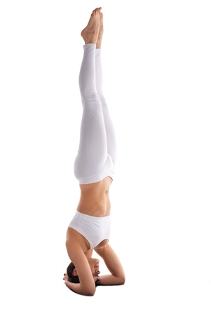 yoga studio: young woman in white stand on head yoga isolated