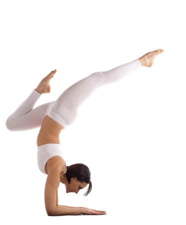 young woman trainer in white cloth stand on hands yoga asana isolated Stock Photo