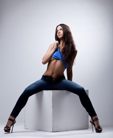 Beauty woman in jeans and tank top posing on cube photo