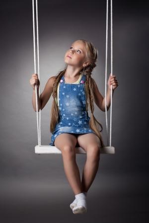 Studio portrait of beautiful blonde girl on swing