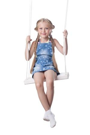 美しいブロンドの女の子のスタジオ ポートレート スイング分離された白の上に座る