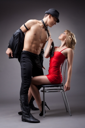strong man show striptease for sexy woman in red Stock Photo - 15044120