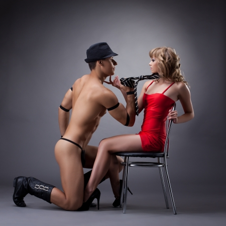 nude athletic man show striptease for sexy girl in red