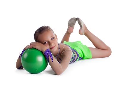 acrobacia: Kid se acostó con pelota verde gimnástico aislado Foto de archivo