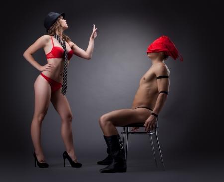 pareja desnuda: mujer sexy en ropa interior de tela roja desvestirse delante de los hombres desnudos Foto de archivo