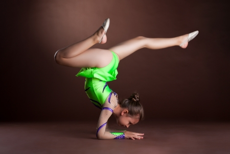 small girl gymnast stand on hands in green costume photo