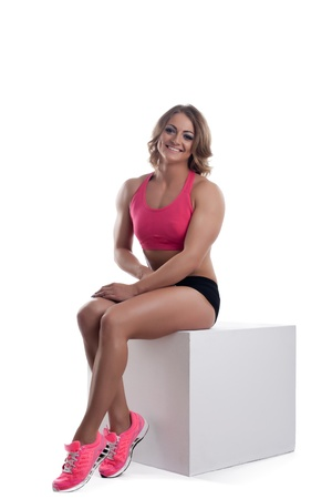 Athletic beauty woman with muscle body sit on cube isolated photo