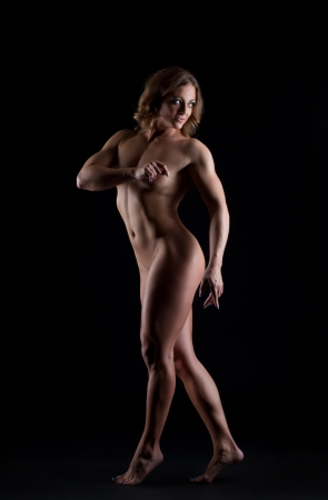 Athletic nude woman bodybuilder posing in dark Stock Photo - 15041113