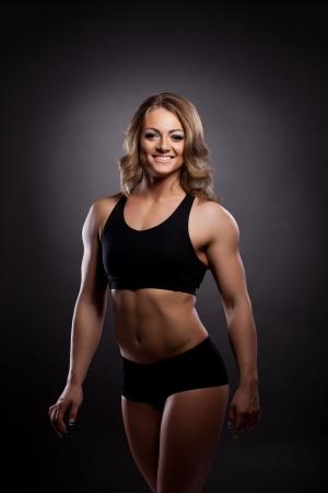 Giovane donna atletica builder corpo, ritratto in palestra costume