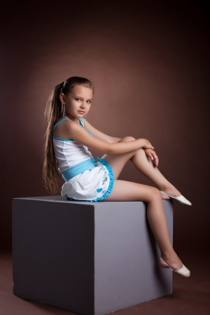 Young child in studio posing on grey cube photo
