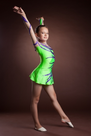 Beauty kid gymnast training in studio - green costume photo