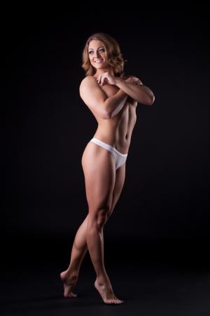 desnudo artistico: Mujer atlética con la carrocería perfecta en bragas blancas posando en la oscuridad Foto de archivo