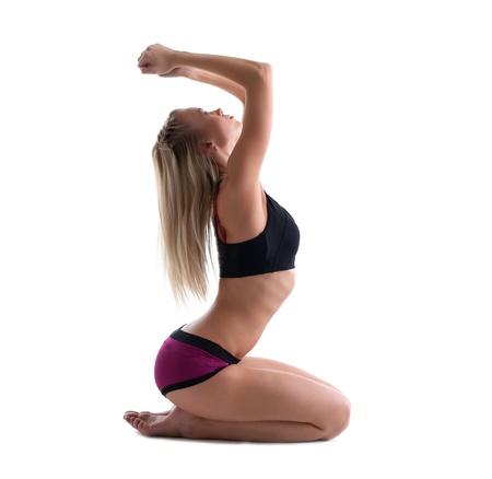gimnasia aerobica: sit joven mujer rubia en pose youga - muestra la figura perfecta