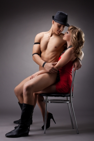 adult sex: striptease playful man flirt with sexy girl in red Stock Photo