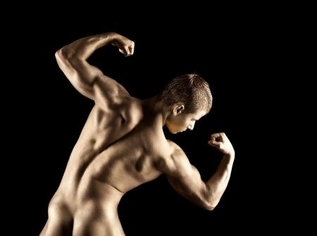naked statue: Nude strong man posing in metallic skin make-up