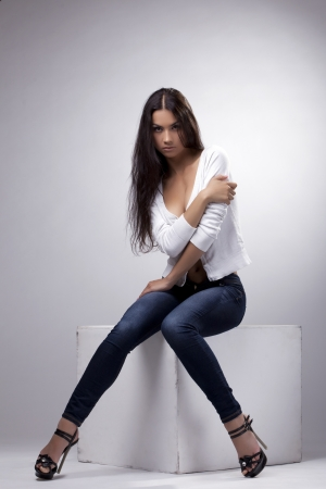 Cute sexy woman sit in jeans and white jacket studio portrait photo