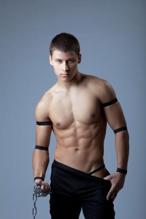 nudo maschile: Giovane uomo ritratto atletico - danza striptease con catena