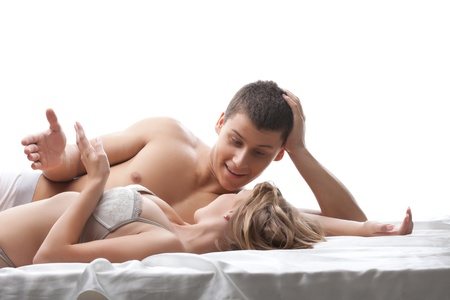 Couple young beauty lovers talk in bed - sexual games isolated Stock Photo - 15419873