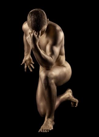 naked statue: Naked strong man posing in metallic skin make-up
