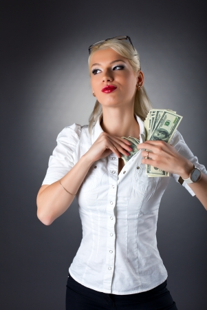 Beauty blond woman hide dollars under shirt photo