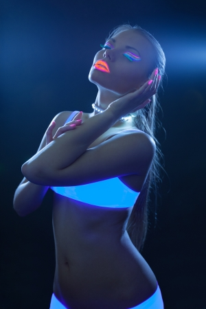 sexy woman with neon make-up dance in ultraviolet photo