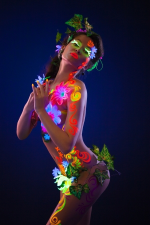 Beauty woman with uv glowing make-up posing in fluorescent light