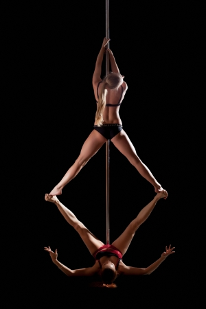 two women show high gymnastic level during pole dance isolated Stock Photo - 16010692