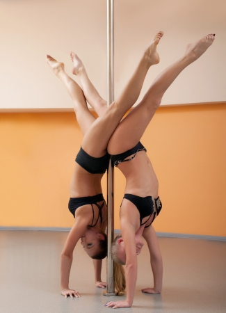 nude gymnast: two athletic girls stand on hands in pole dance in training room