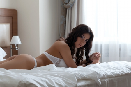 women in underwear: Beautiful brunette woman posing in white sexy lingerie Stock Photo