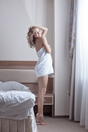 sexy blond woman wearing towels on her body in morning bedroom photo