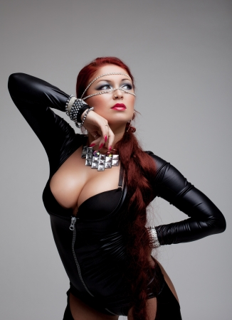 fetishes: Studio portrait of sexy woman in latex costume and red plait Stock Photo